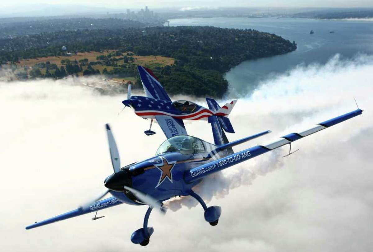 John Klatt in the Air National Guard Extra 300L, bottom, and Bill Kerns in the Air Guard Staudacher, top, fly over a fog bank on Thursday. Stunt planes have taken to the skies of Seattle in preparation for Seafair's Boeing Air Show over Lake Washington.