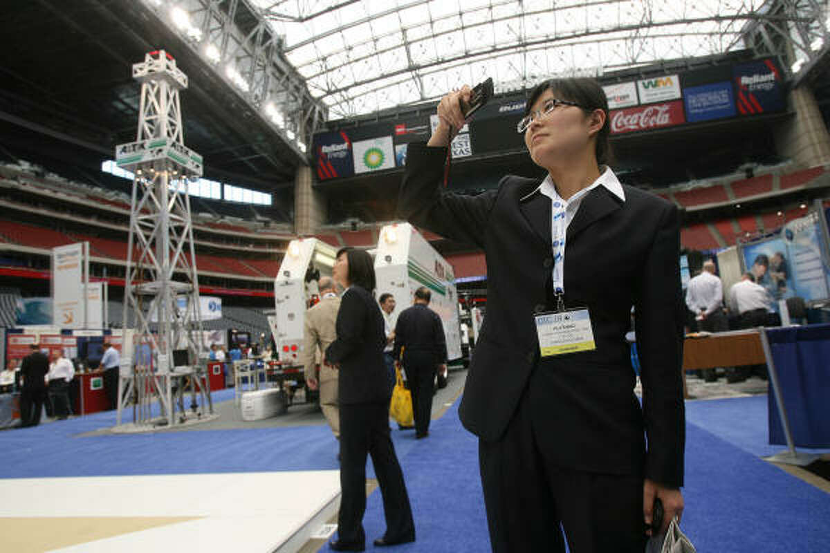 Hui Shao, of Jiangsu Changbao Steel Tube LTD of Changzhou, China, photographs exhibits inside Reliant Stadium on the first day of the Offshore Technology Conference.