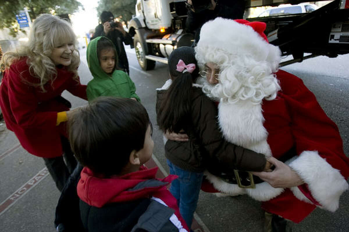Santa was on hand to greet youngsters as Superfeast setup began Wednesday. Jazline Salines, 6, gives him a hug as Carlos Cano, 3, and his sister, Jacqueline, 5, wait their turn.