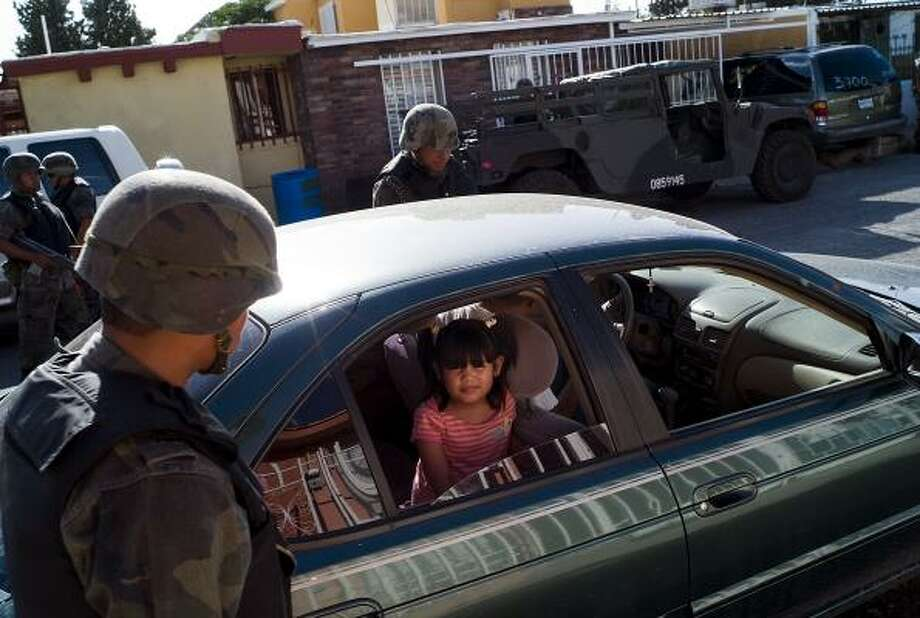 Soldiers stop a family's car in a Juarez neighborhood checkpoint. Roadblocks with vehicle searches have become commonplace as the city lives under military occupation meant to bring peace to the troubled city across the border from El Paso. Photo: Julian Cardona, For The Chronicle