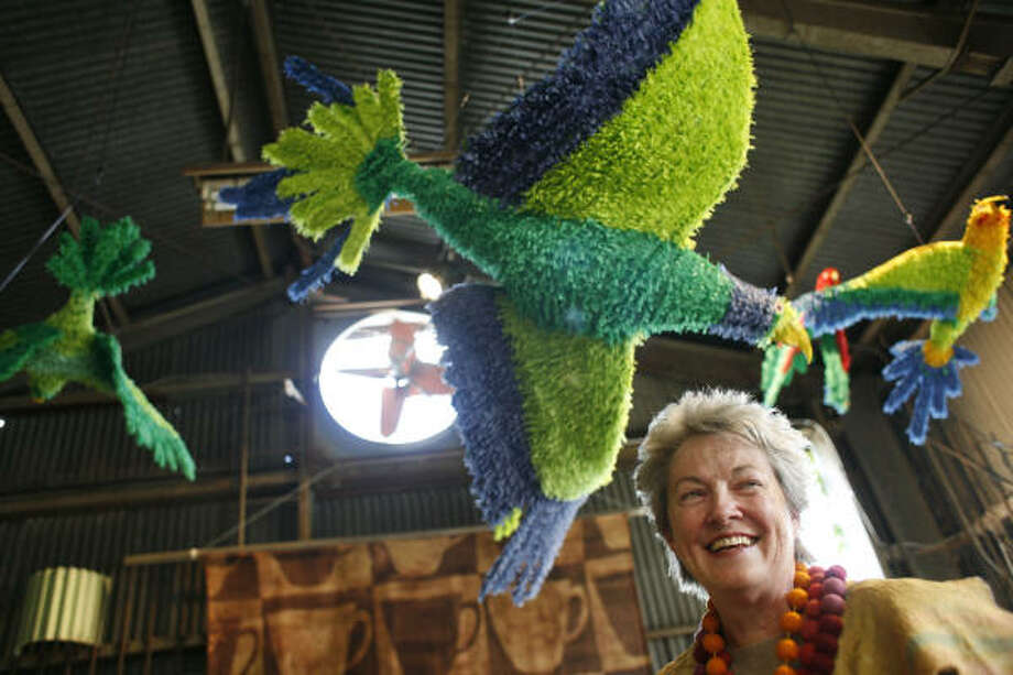Mary Margaret Hansen stands below Victor James Rodriguez's East End Flying Feral Parrot Flock inside Second Seating. Photo: Eric Kayne, For The Chronicle