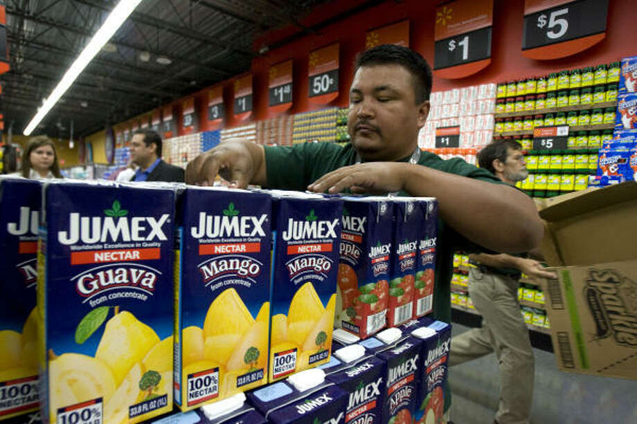 Supermercado de Walmart employee Cruz Sanchez stocks juice at the new store, a Hispanic-focused supermarket from Wal-Mart Stores. Photo: JOHNNY HANSON :, CHRONICLE