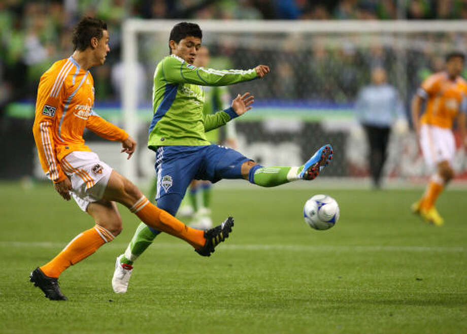 Seattle's Fredy Montero, right, tries to get control of the ball from Dynamo defender Geoff Cameron during the first half of Thursday's first-round match at Qwest Field in Seattle. Photo: Joshua Trujillo, Seattlepi.com
