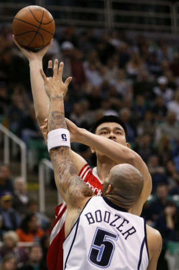 Yao Ming, back, shoots over Jazz forward Carlos Boozer in the first half. Photo: Colin E. Braley, AP