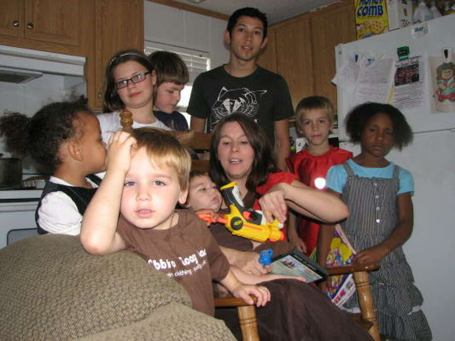GROUP SHOT: Melissa Beach sits and holds 1-year-old Jeremiah while surrounded by some of the 13 children she is currently caring for at home. Pictured counterclockwise from the front is Jacob, 3 Grace, 3, Faith, 12, Paul, 13, Jose, 19, Justin, 7, and Hope, 8. Photo: DIANA NORTH, FOR THE CHRONICLE