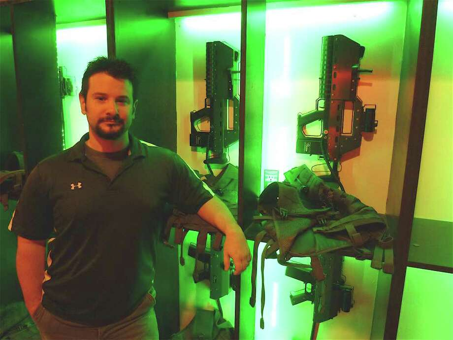 Keith DiBuono, owner of First Person Sports, stands beside a rack containing mesh military-style vests and AK-47 tagger guns that rely on infrared light technology for the gamer business in Fairfield. Photo: Mike Lauterborn / Fairfield Citizen contributed