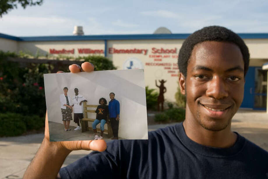 Eagle Scout Tom Soda of Richmond shows a photograph made when he presented his Eagle Scout project, a playground bench, to his alma mater, Manford Williams Elementary School.  Shown in the photo are then principal Holly Haynes, Soda, 14 at the time; Soda's sister Toluse Soda, then 11, and Soda's mother Bola. Photo: R. Clayton McKee, For The Chronicle