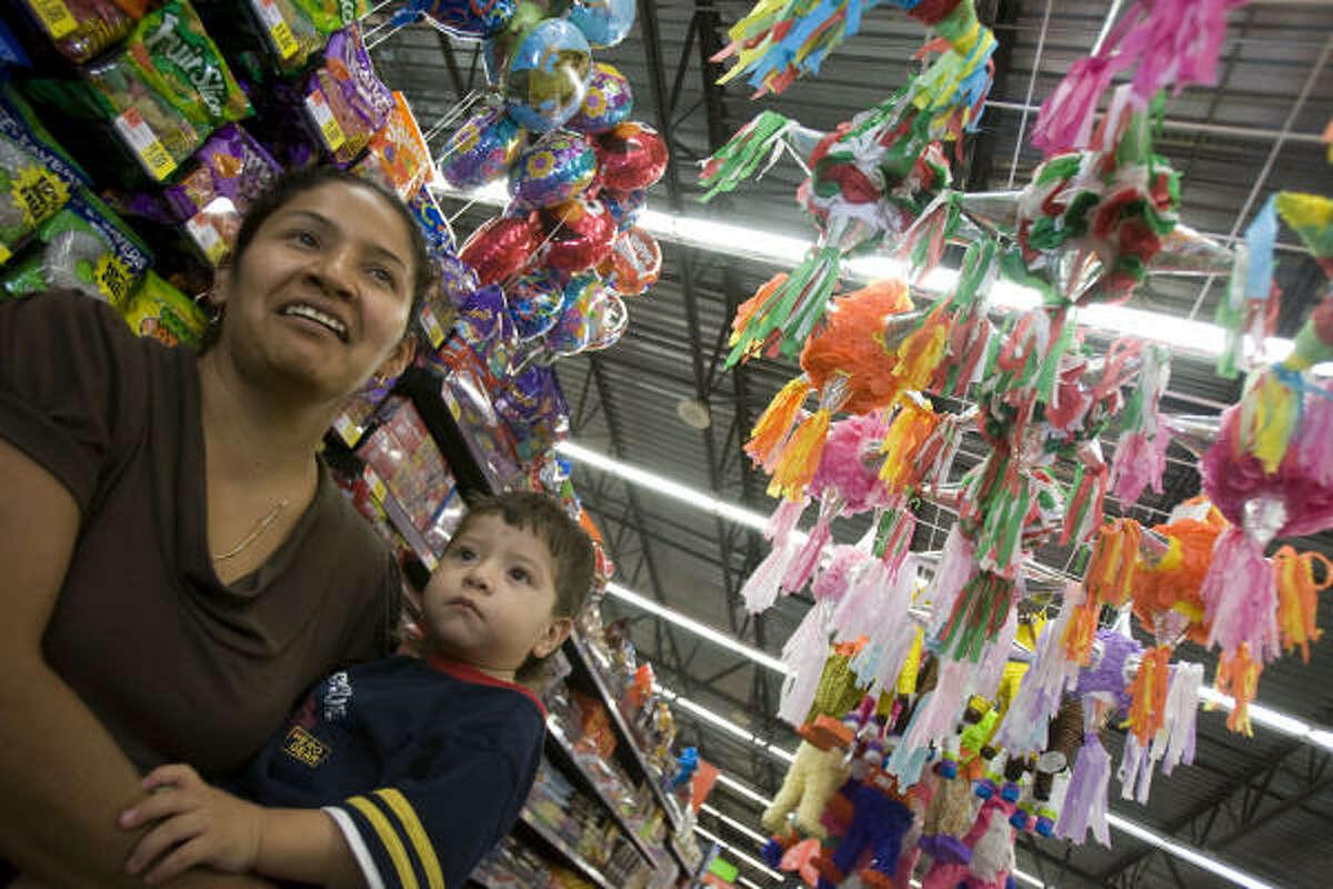 Shopper Rayna Soto and her son Alex Cervantes take in Supermercado de Walmart's piñata-decorated candy aisle.