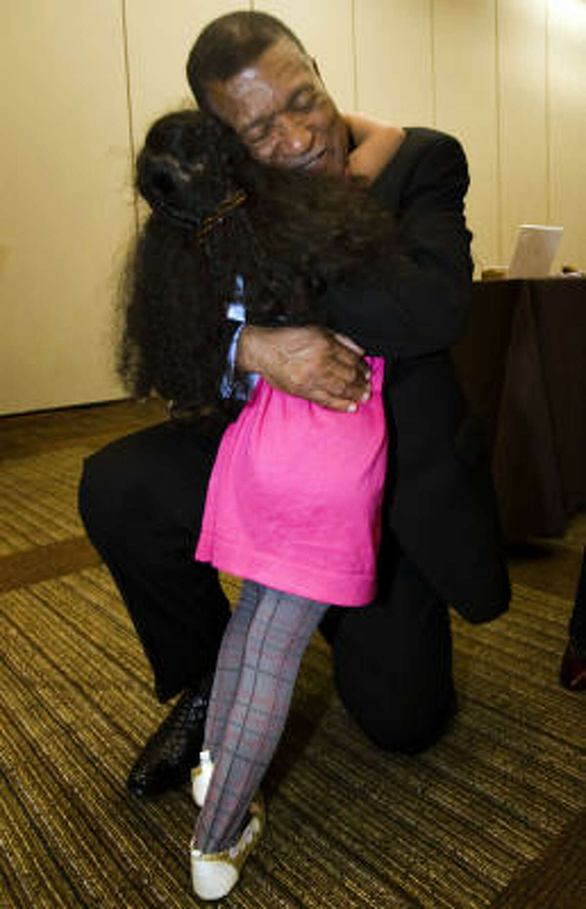 Gene Locke hugs his granddaughter Zoela Gullo, 4, at the downtown Hyatt Regency. He said the runoff is the latest uphill battle in his life.