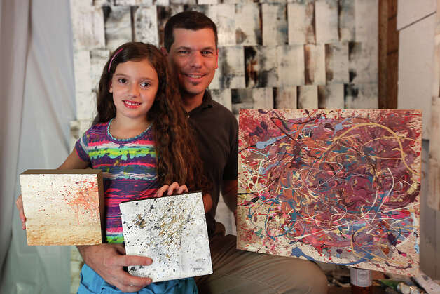 Bella Stephenson, 8, and her dad, Russell Stephenson, display some of Bella's abstract paint splatter art in her dad's home studio. JERRY LARA / EXPRESS-NEWS / SAN ANTONIO EXPRESS-NEWS
