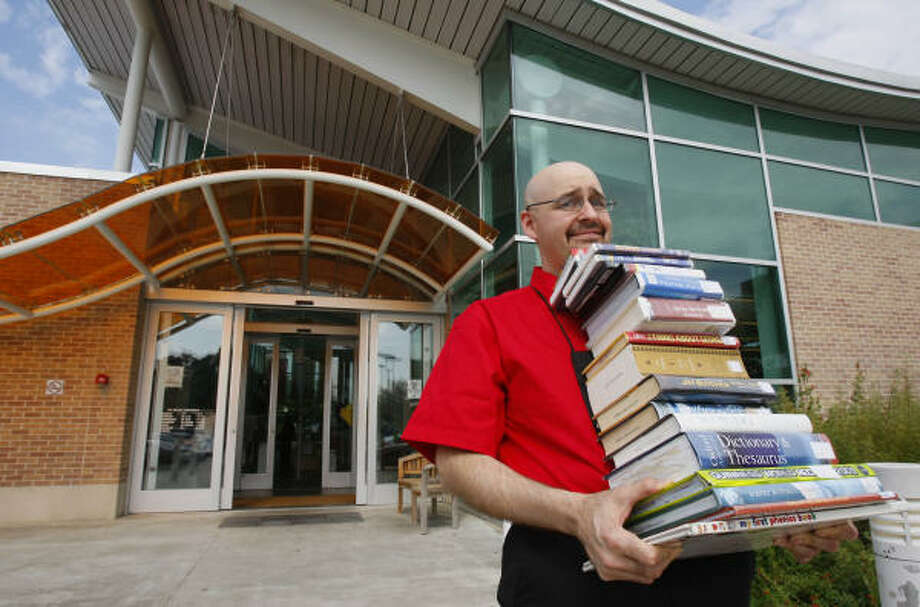 John A. Merullo, manager of the McGovern-Stella Link Branch Library, demonstrates how the new HPL To Go curbside service would work at parking space-poor branches. Photo: Mayra Beltran, Chronicle