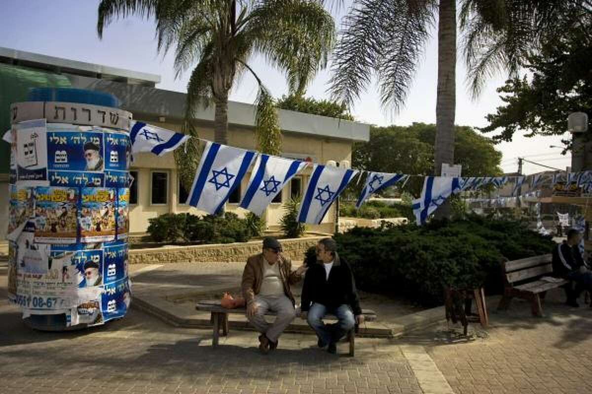 Israeli flags are seen as Israelis talk in a street at the southern Israeli city of Sderot, Sunday.