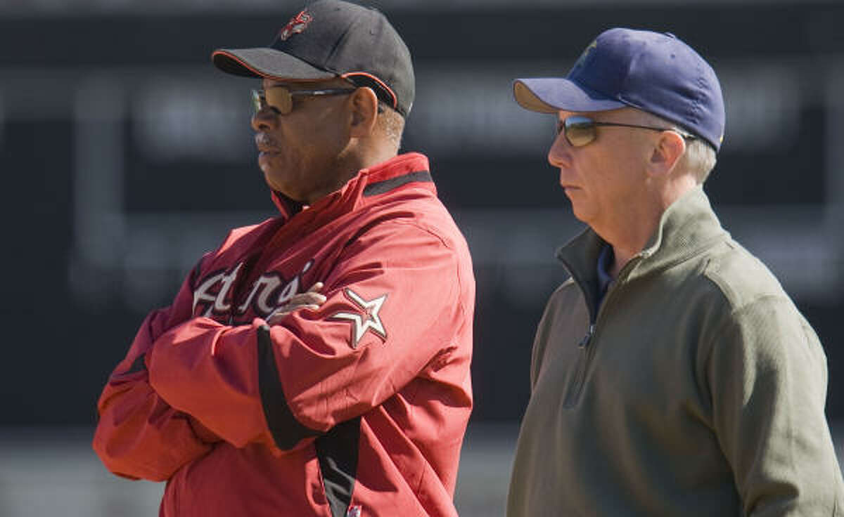 Astros manager Cecil Cooper, left, isn't solely to blame for the team's troubles, said General Manager Ed Wade, right.