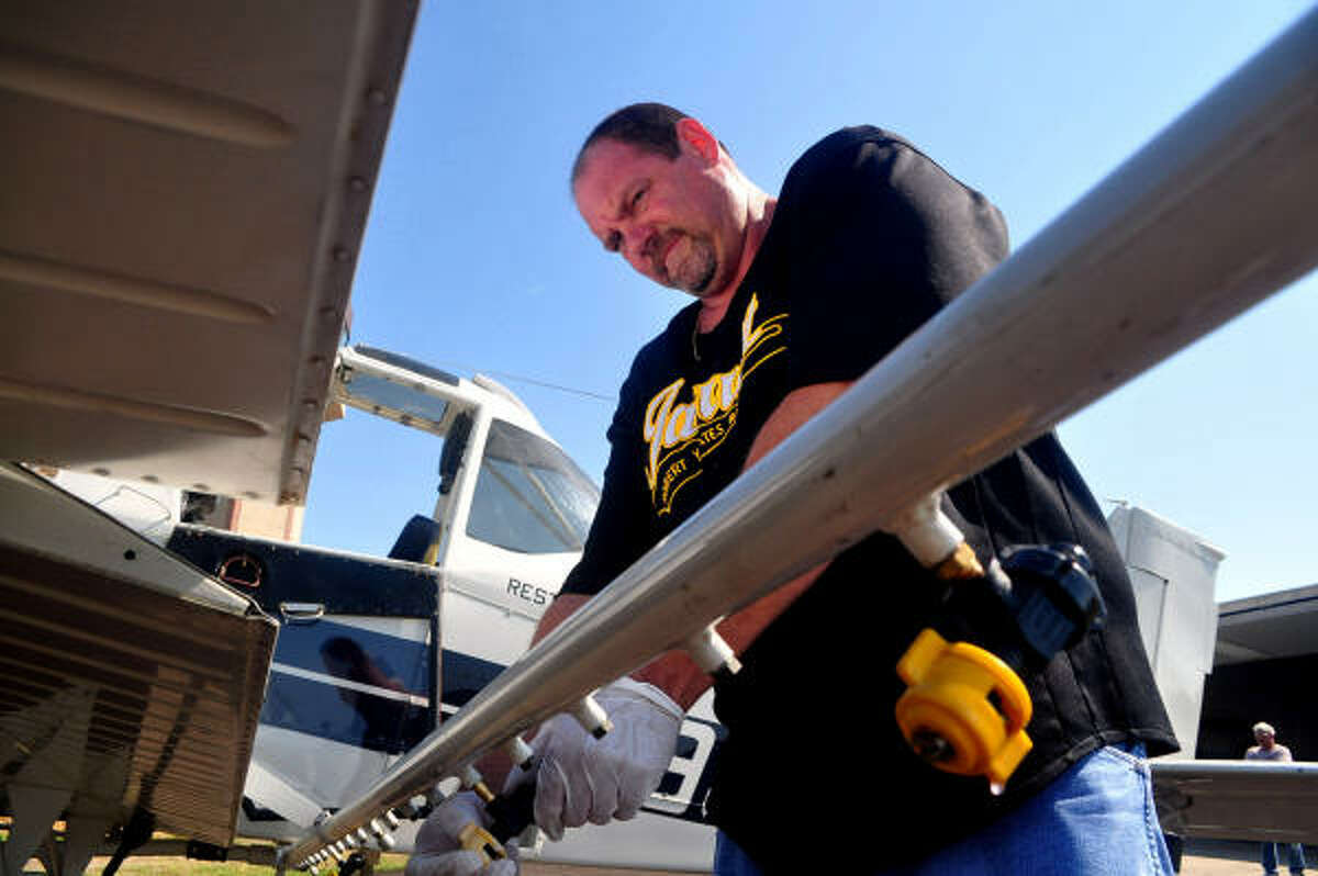 GETTING READY: Rufus Barnnett of the Galveston County Mosquito Control District works on one of the nozzles that releases the mosquito spray from the mosquito-control airplane.