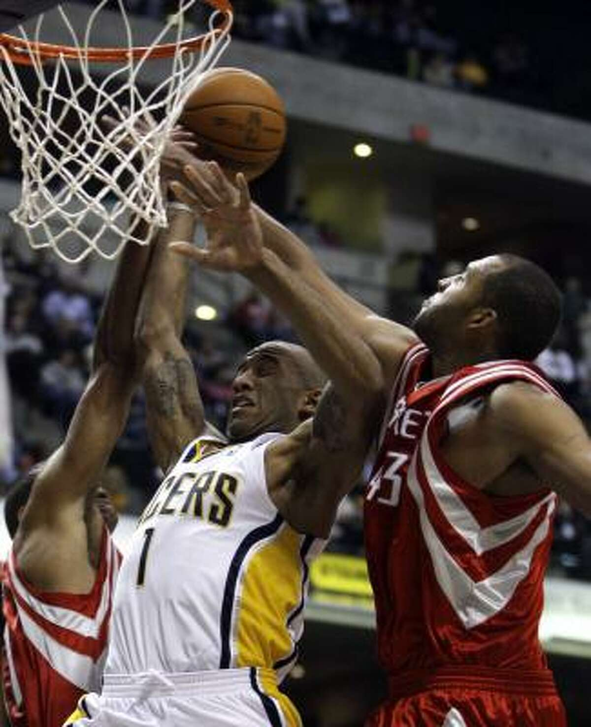 Pacers guard Dahntay Jones (1) puts up a shot against Rockets forwards Shane Battier, left, and Brian Cook in Friday's game.