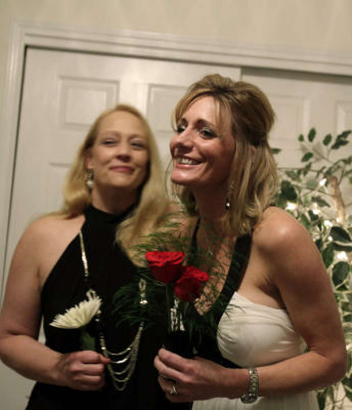 """Supported by her sister-in-law, Tamé Howard, left, Lanessa Lawrence, 35, says """"I do"""" as she marries Matt Howard, looking on by Skype from Afghanistan, on Thursday."""