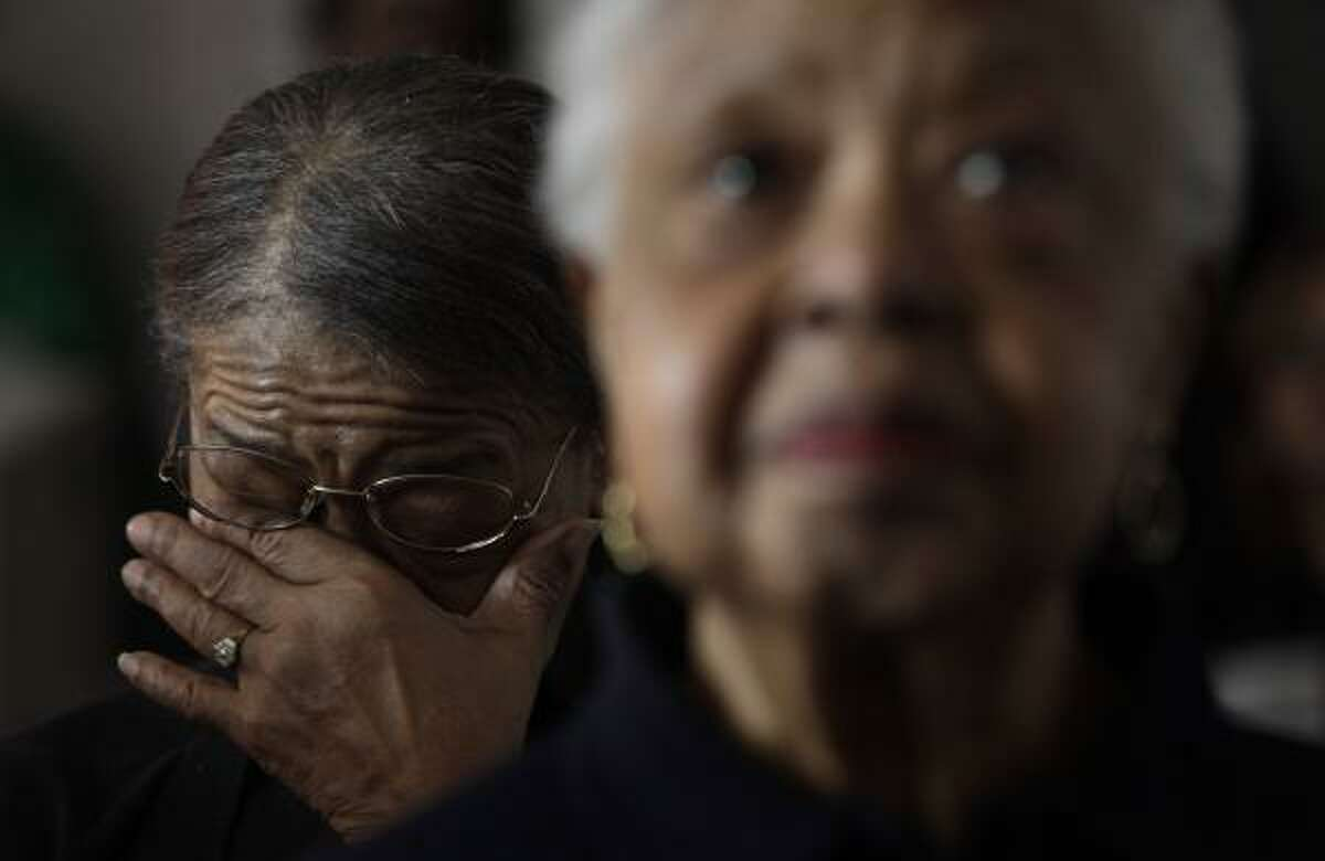 DETROIT BARACK CITY: Mary K. Jones, 78, top, anticipates the historic moment when Barack Obama takes the oath of office at Hannan House in Detroit, and afterward, Ella Crawford, 73, above, wipes away tears.