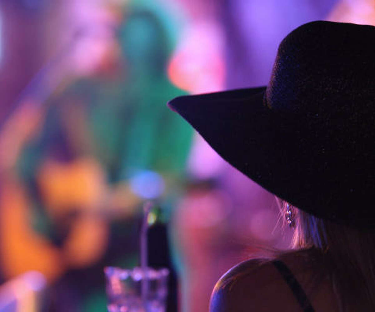 A woman watches Kevin Higgins of the Dust Devils perform at The Back Porch Bar.
