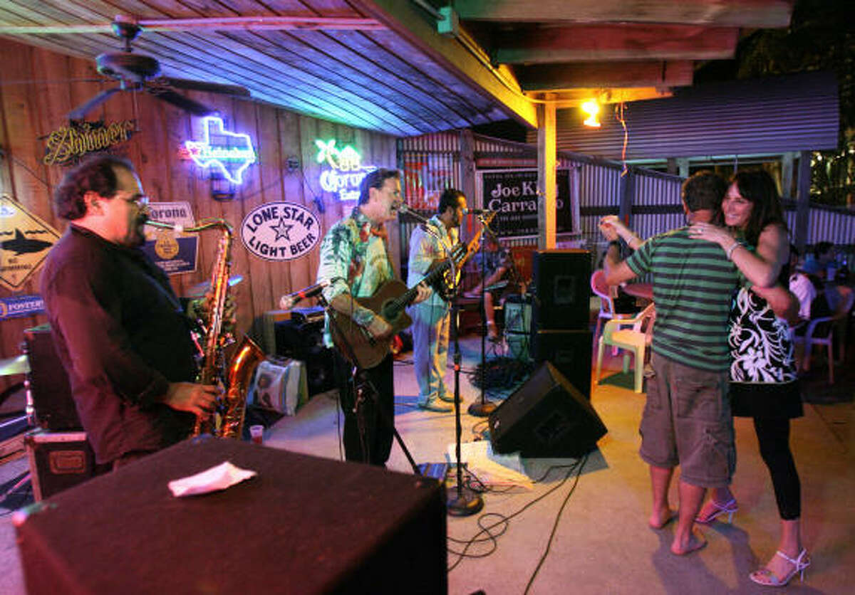 Joe King Carrasco, second from left, gets dancers to kick up their heels — and one to kick off his shoes — with his Tex-Mex tunes at The Back Porch Bar in Port Aransas.