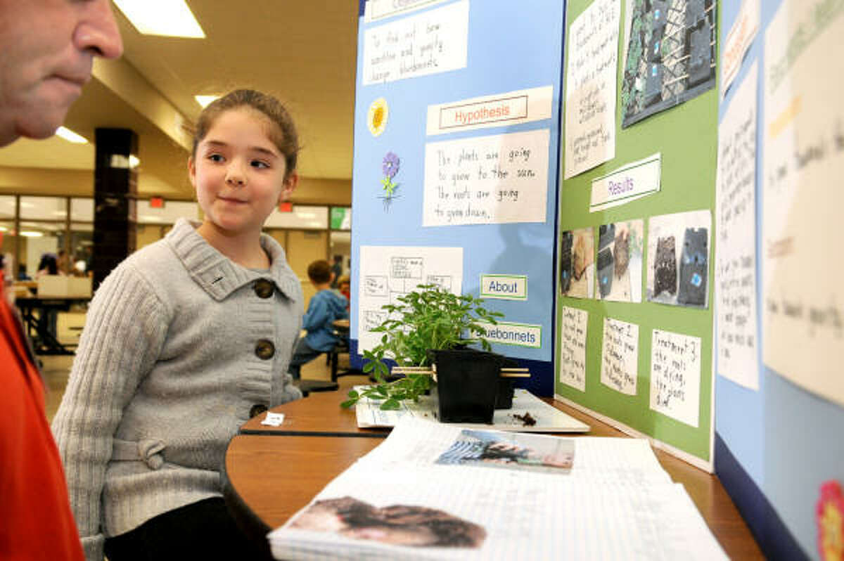 """WATCH AND LEARN: Maya Havwood, 6, a first-grader at Shadowforest Elementary, explains her project, titled """"Growing Texas Bluebonnets"""" during the judging of the Humble school district elementary science fair at Humble High School on March 28."""