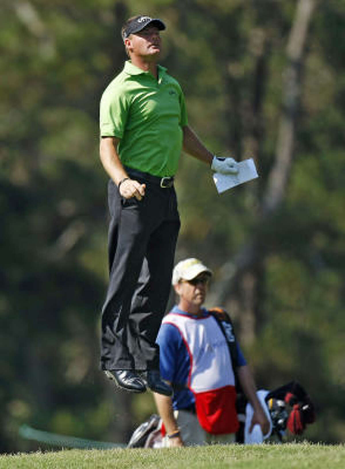 TPC leader Alex Cejka jumps to get a better view of the 12th hole.