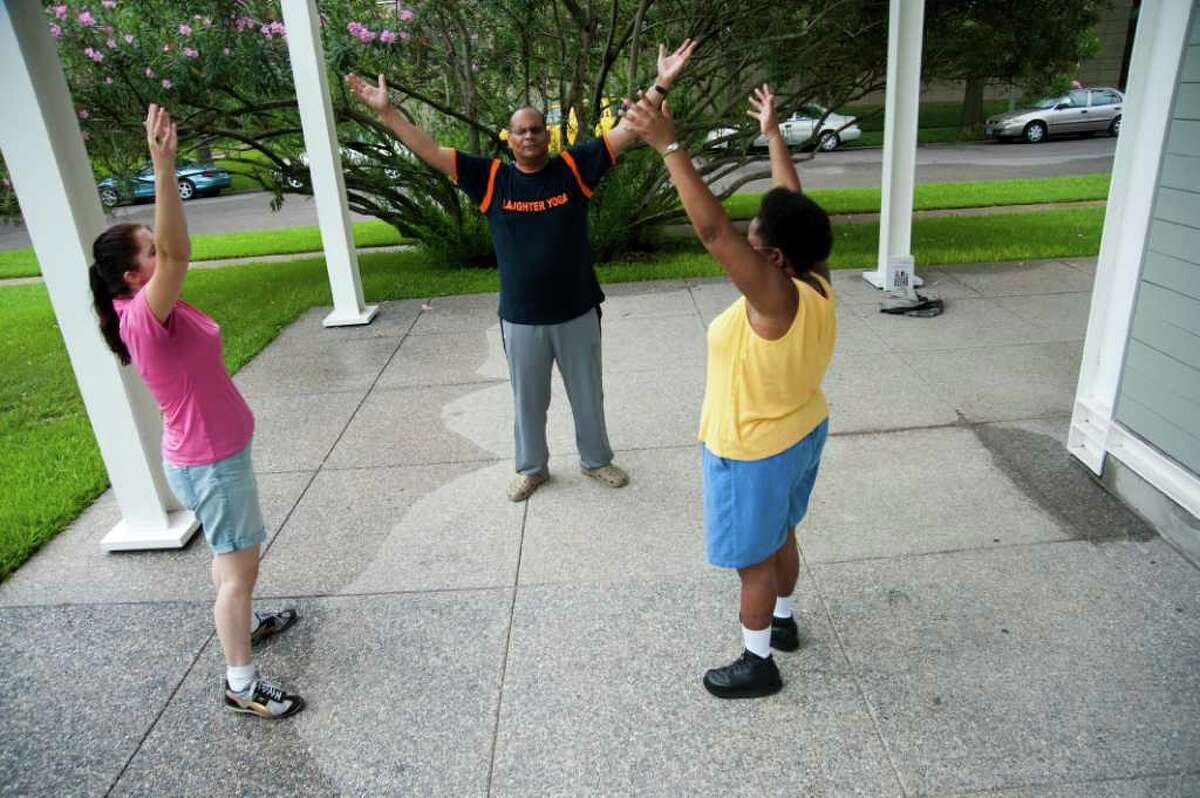 HOUSTON- Elanore Crystal Cornell, right, participates in laughter yoga with Stephen Findley and Lainie Diamond in Menil Park July 18, 2011.