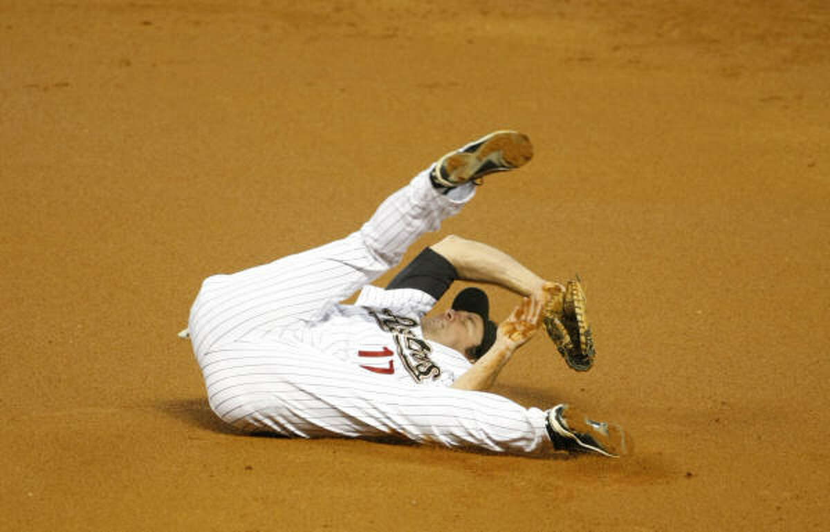 Lance Berkman rolls after diving for a hard shot in the second inning.