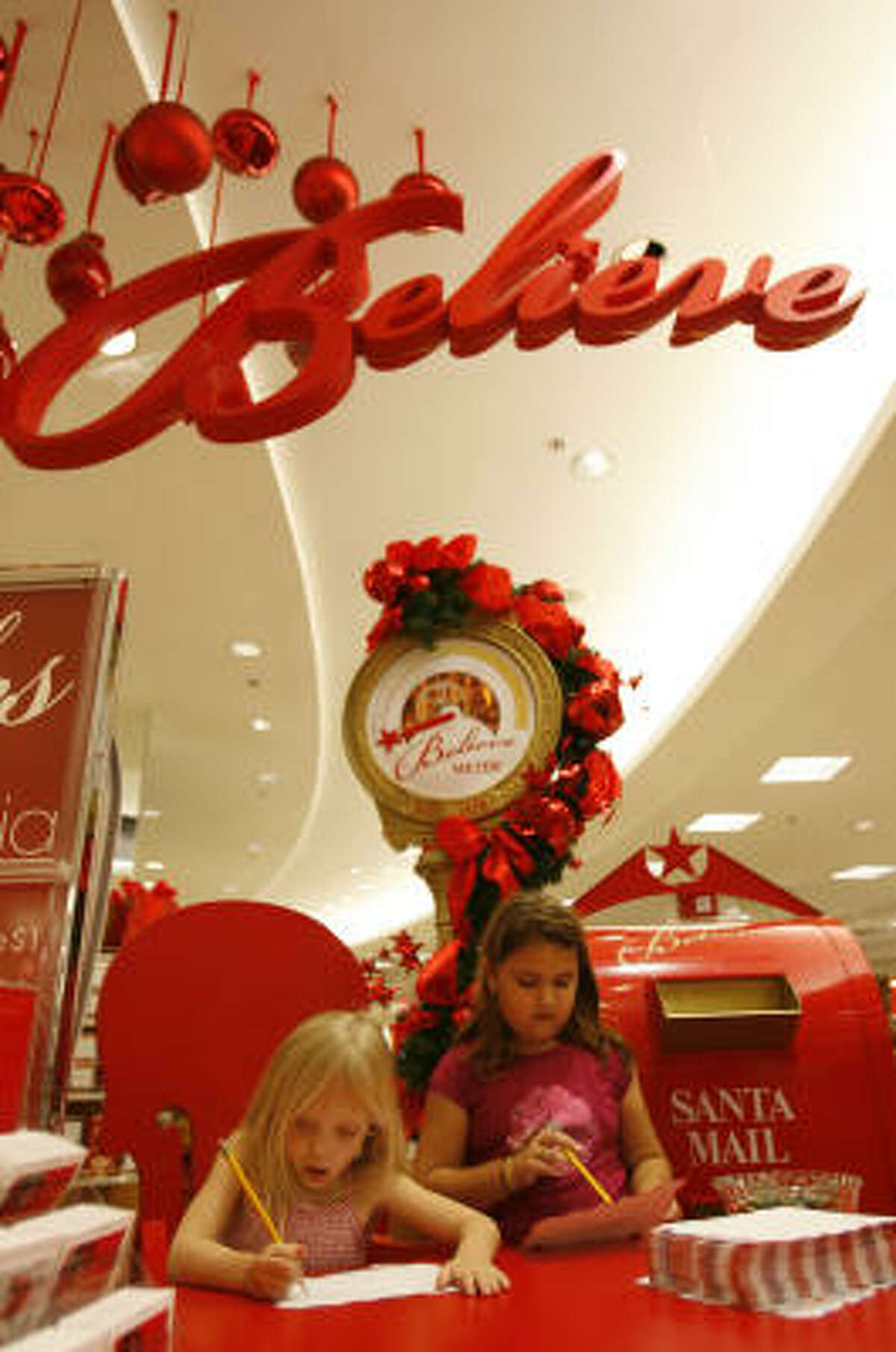 "Ava Ramon, 5, and her sister, Alina Ramon, 8, write letters to Santa at the ""Believe"" station at Macy's in the Memorial City Mall, part of the retailer's fundraising project."