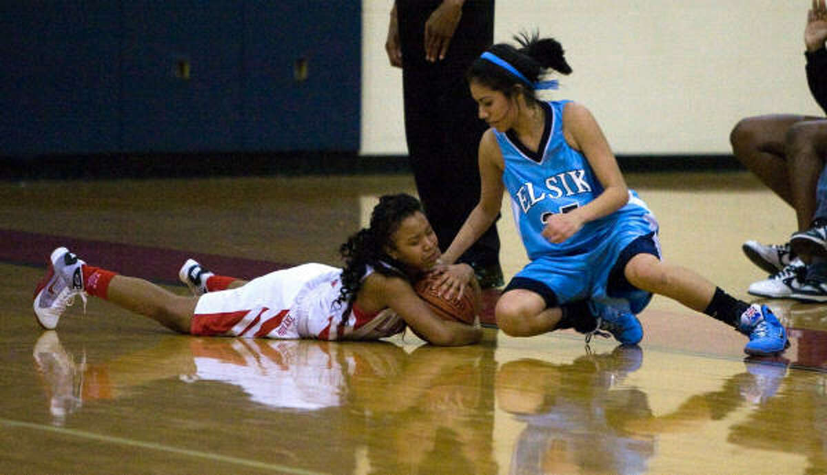 Alief Taylor guard Victoria Williams, left, and Elsik guard Jazmine Ocanas (25) go to the floor for a loose ball.