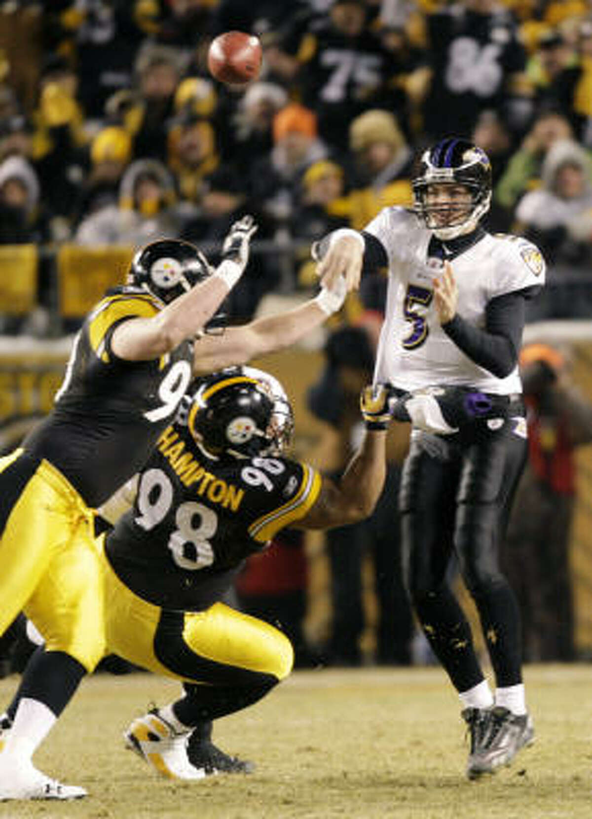Ravens quarterback Joe Flacco throws over Steelers defensive linemen Aaron Smith and Casey Hampton while avoiding a sack during the first quarter.