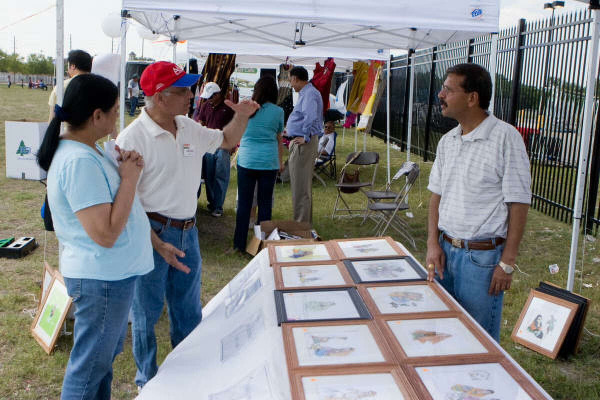 Kirti and Chad Patel discuss art with artist Sharad Mathur at the recent India House Community Carnival.