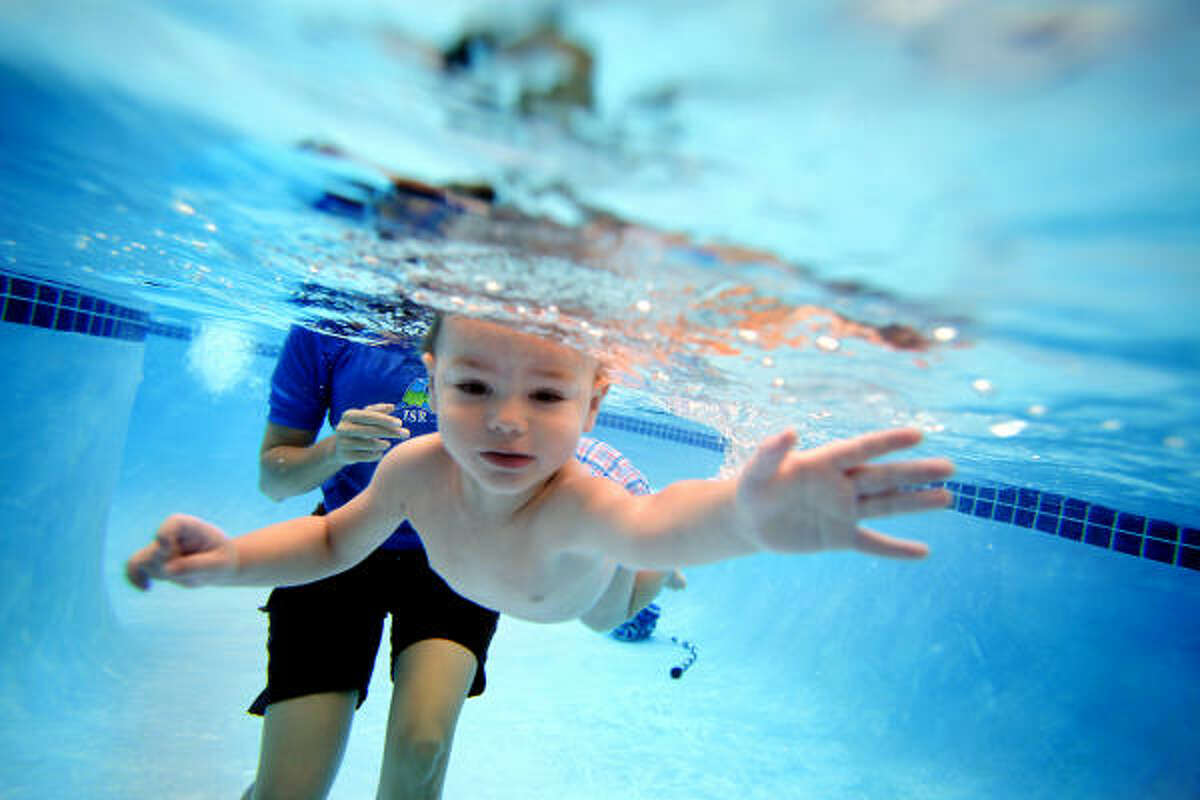 "Joshiah White-Mote, 2, dives under the water during a swimming lesson. His mother, Rachel White, said she enrolled him to gain a sense of security around his grandparents' pool. ""Yesterday and today is the first day he hasn't been crying,"" she said."