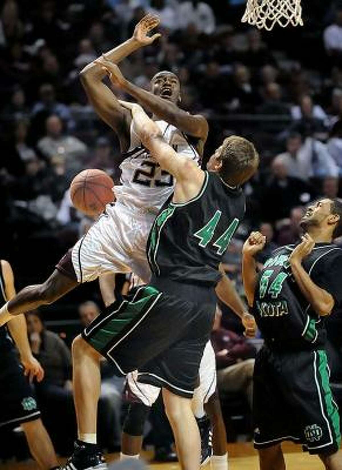 Texas A&M's Josh Carter (23) is fouled by North Dakota's Derek Benter (44) as Darius Joseph (54) looks on during the first half on Monday.
