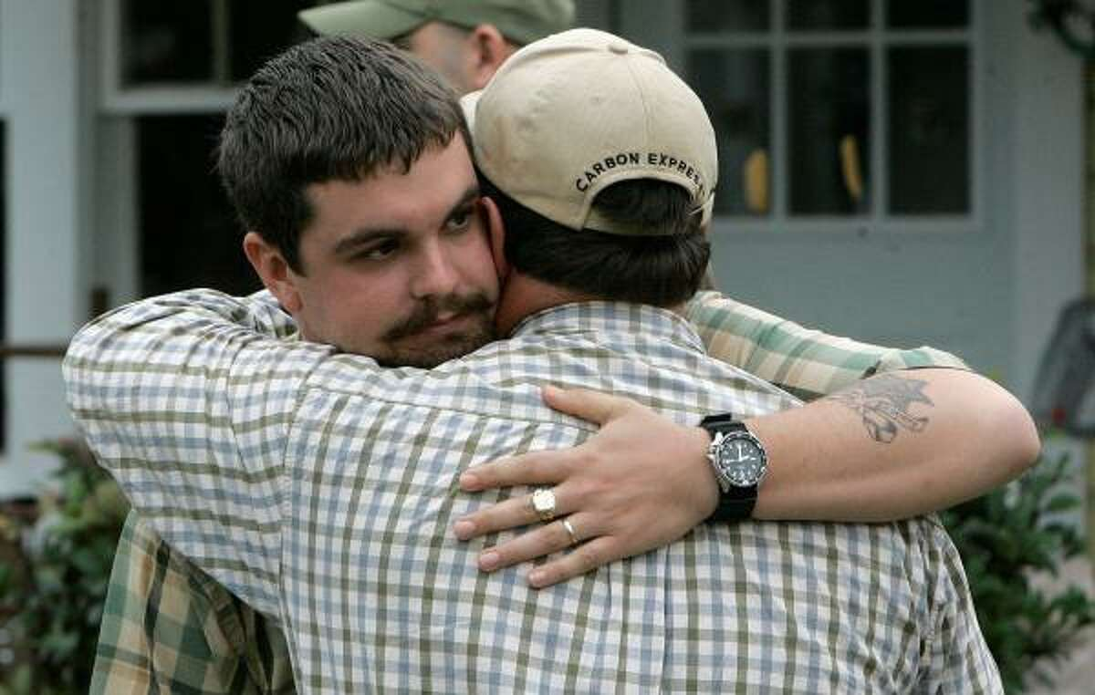 Josh Myers, left, a deputy with the Geneva County Sheriff's department whose wife and daughter were killed in a Tuesday shooting in Samson, is consoled by a friend, Wednesday, March 11, 2009, in Samson, Ala. The family was killed in a house across the street from their home on Tuesday.(AP Photo/Phil Coale)