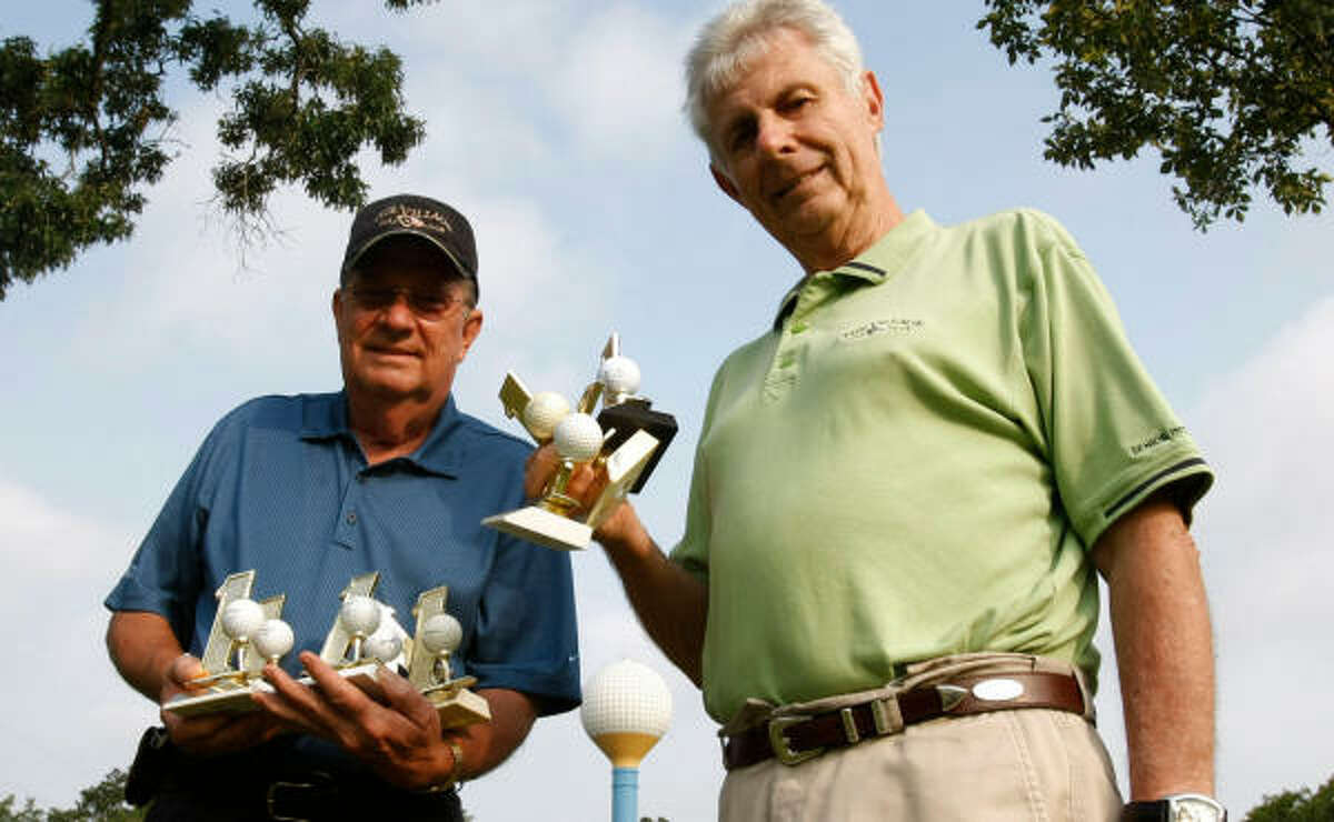 Walter Plagens, left, and Lloyd Austin have so many trophies from holes-in-one they can barely hold them.