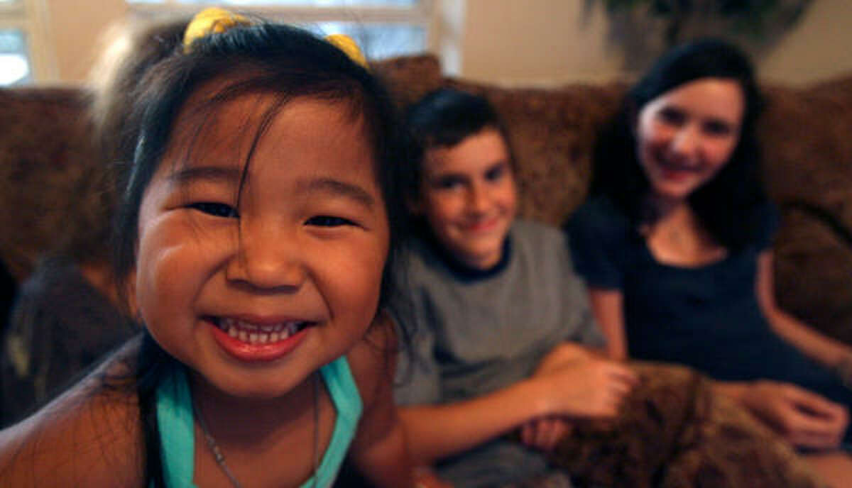 Sioban McGrath, 3, from Jianxi, China, was adopted by the McGrath family of San Antonio. In the background are Liam McGrath, 12, and Regan McGrath, 14.
