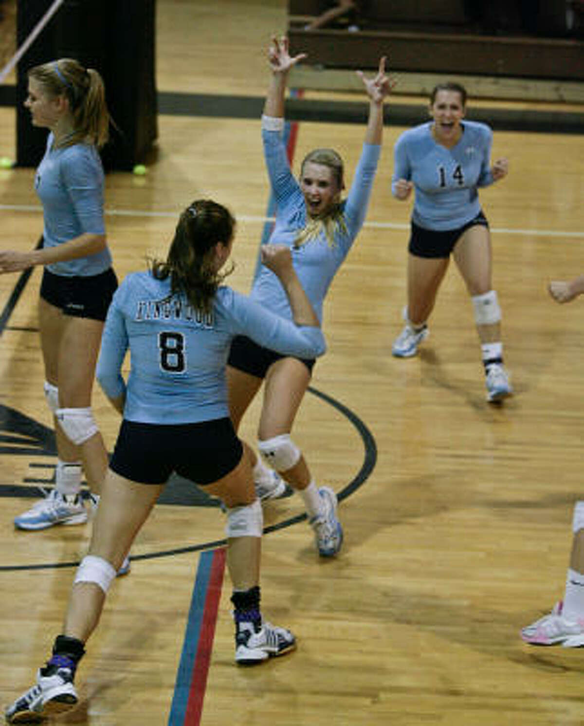 Kingwood players celebrate a point during their sweep of Eisenhower on Tuesday night.