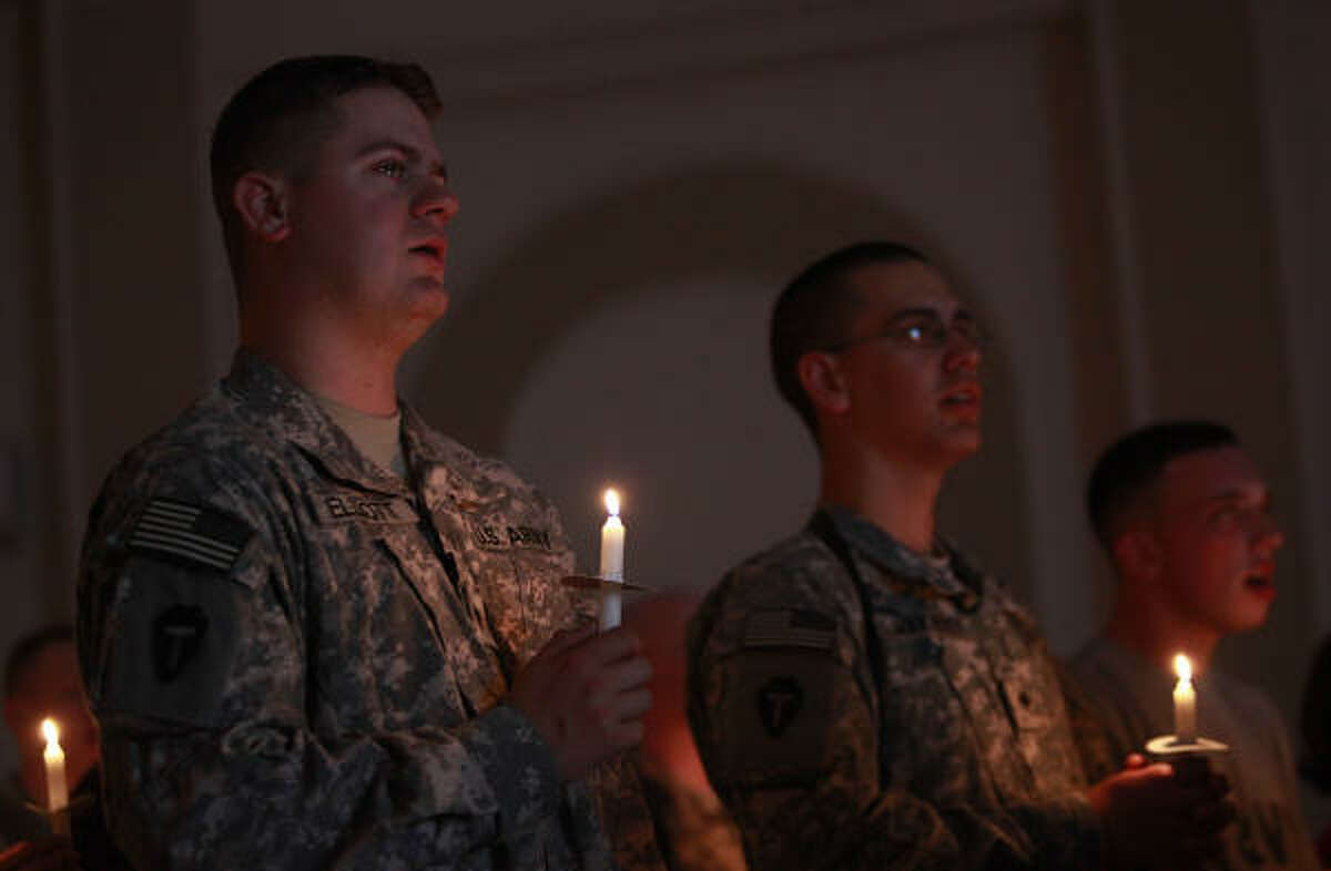 "Spc. Garrett Elliott, 23, of Houston, left, holds back tears while singing Silent Night during a service in the Palace Chapel at Camp Prosperity on Christmas Eve in Baghdad. ""It's my first Christmas away from my family,"" he said."