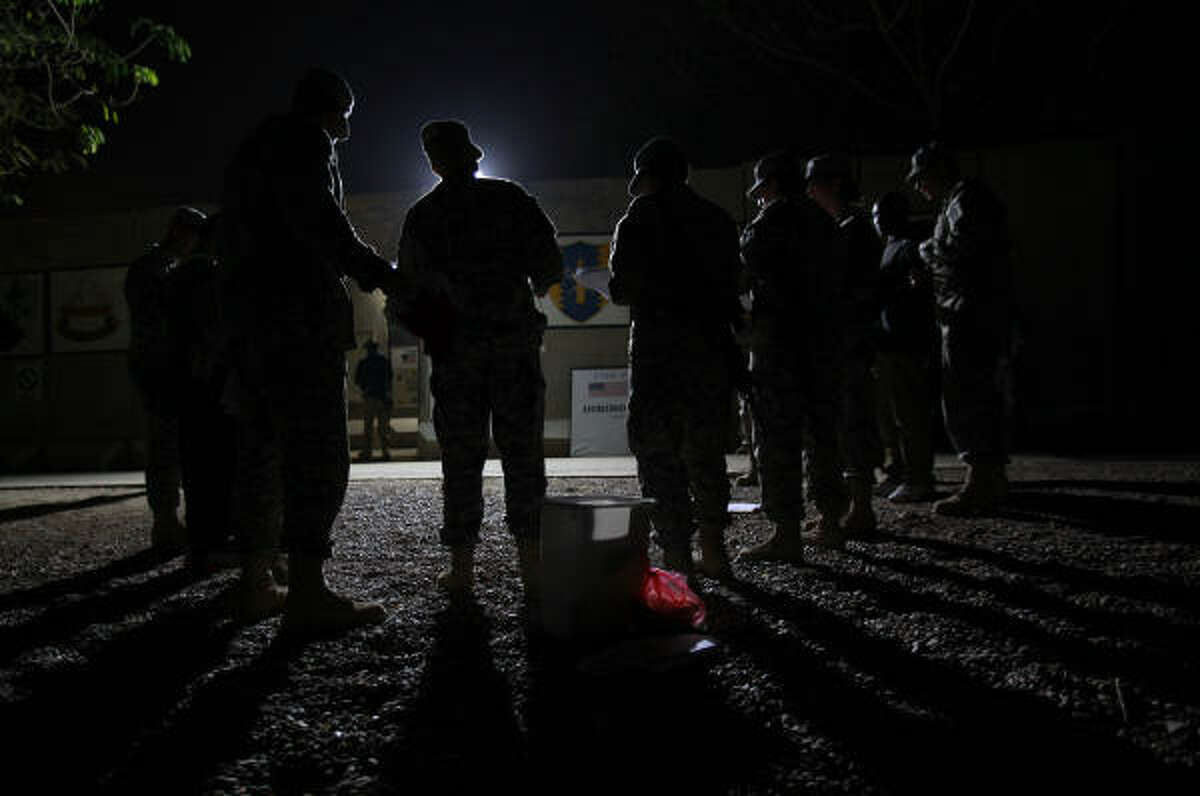 Troops with the Texas National Guard's 72nd Infantry Brigade Combat Team sing Christmas carols outside the dining facility at Camp Prosperity on Christmas Eve In Baghdad.