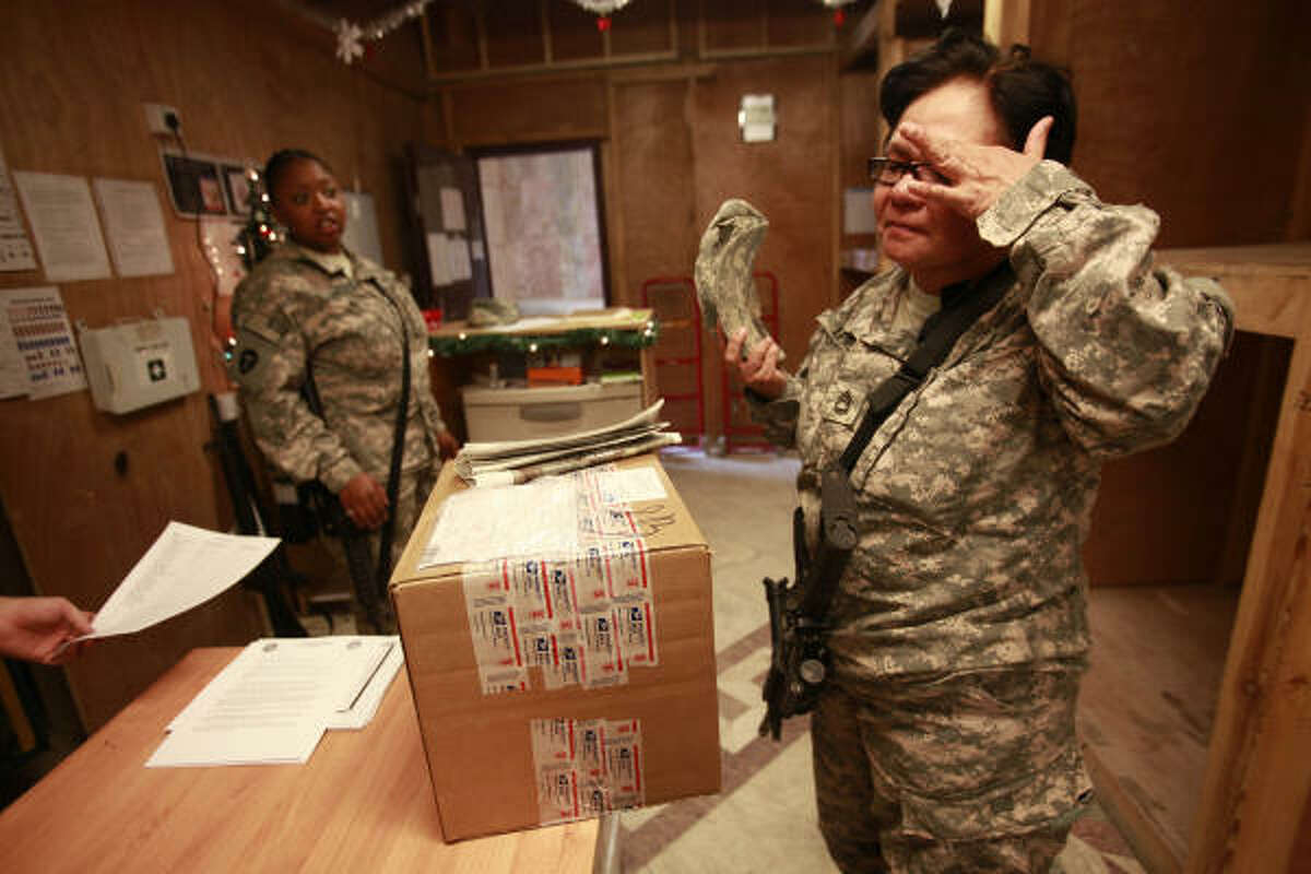Sgt. 1st Class Carlota Levine, 54, of San Antonio, tears up as she picks up a Christmas package from the mailroom at Camp Prosperity on Christmas Eve.
