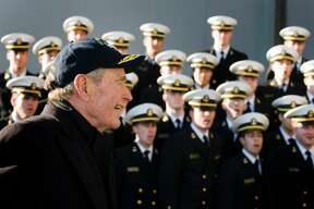 Former President George H.W. Bush is serenaded by a Navy choir as he steps aboard the service's newest aircraft carrier, the USS George H.W. Bush, for a tour Friday in Norfolk, Va.