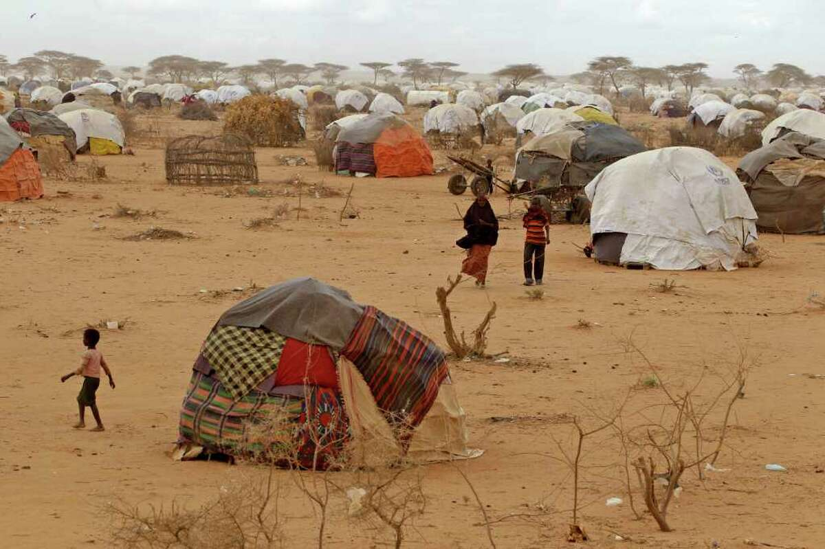 People at a refugee camp in Dadaab, Kenya, Thursday, Aug 4, 2011. Dadaab, a camp designed for 90,000 people now houses around 440,000 refugees. Almost all are from war-ravaged Somalia. Some have been here for more than 20 years, when the country first collapsed into anarchy. But now more than 1,000 are arriving daily, fleeing fighting or hunger(AP Photo/Schalk van Zuydam)