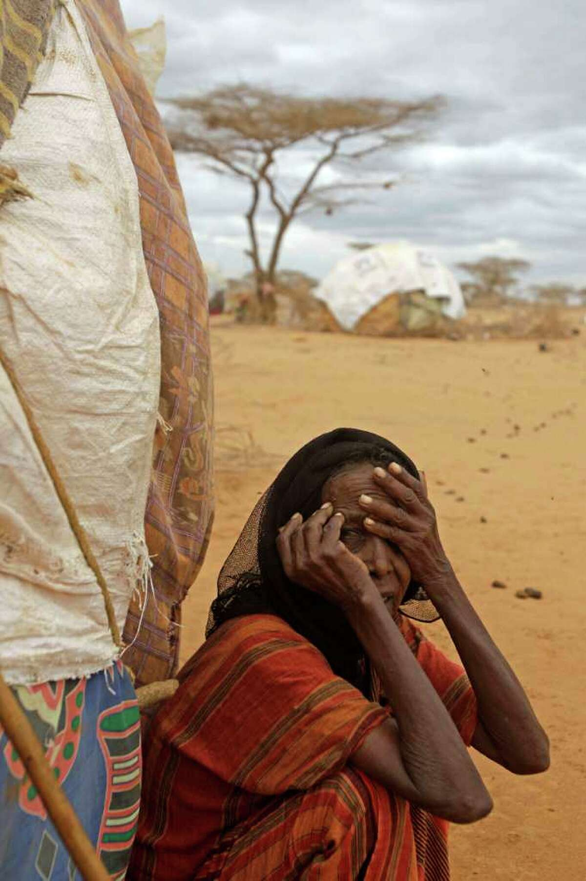 A old woman sits in front of her home at a refugee camp in Dadaab, Kenya, Thursday, Aug 4, 2011. Dadaab, a camp designed for 90,000 people now houses around 440,000 refugees. Almost all are from war-ravaged Somalia. Some have been here for more than 20 years, when the country first collapsed into anarchy. But now more than 1,000 are arriving daily, fleeing fighting or hunger(AP Photo/Schalk van Zuydam)