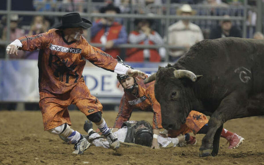 Bullfighter Cory Wall lures the bull away from rider Brent Menz, who is shielded by Clay Collins on Sunday. Menz was briefly unconscious and got 15 stitches. He wasn't hospitalized.  Photo: Melissa Phillip, Chronicle