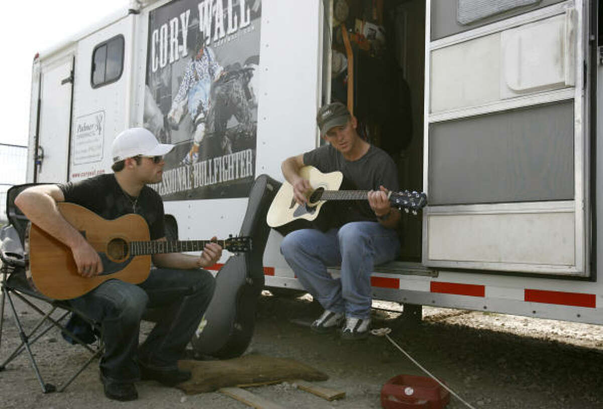 Dusty Tuckness, 22, left, and Cory Wall relax at his trailer Sunday. Wall, 40, has been a bullfighter for 19 years.