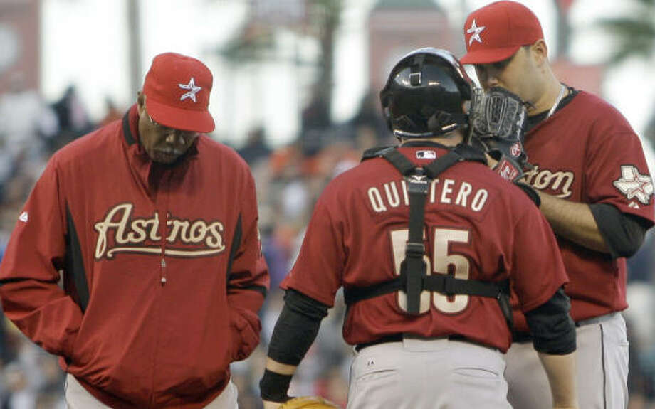 Felipe Paulino, right, chats with manager Cecil Cooper, left, and catcher Humberto Quintero during the first inning. Photo: Ben Margot, AP