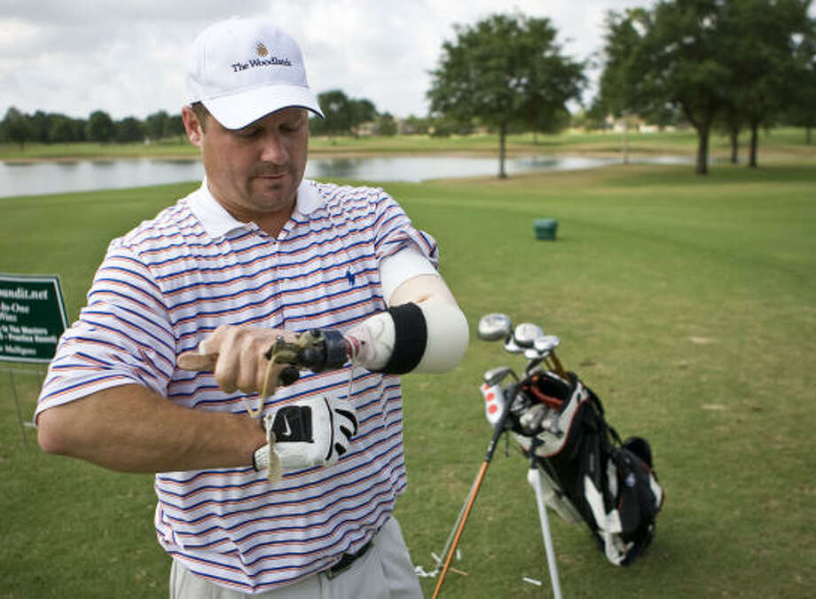 Larry Alford adjusts the prosthesis that allowed him to continue golfing despite a devastating car accident at age 18. Photo: Nick De La Torre, Chronicle