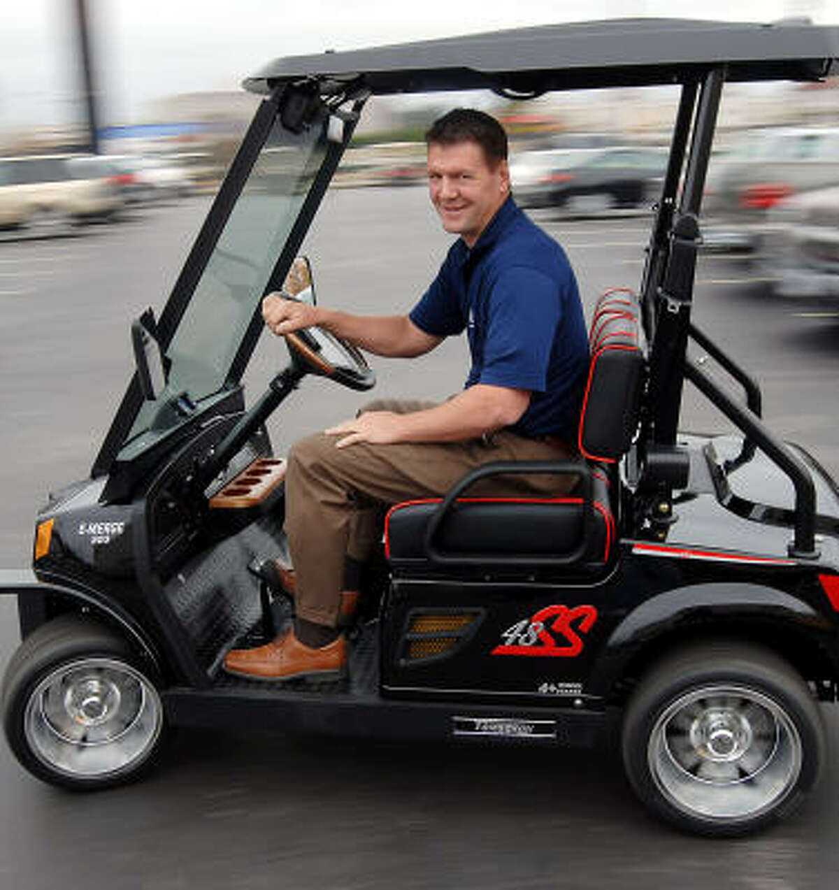 """Derek Severns, co-owner of Golf Cars of Houston, drives a neighborhood electric vehicle. """"A golf car is something you drive, a cart is something you pull,"""" he says."""