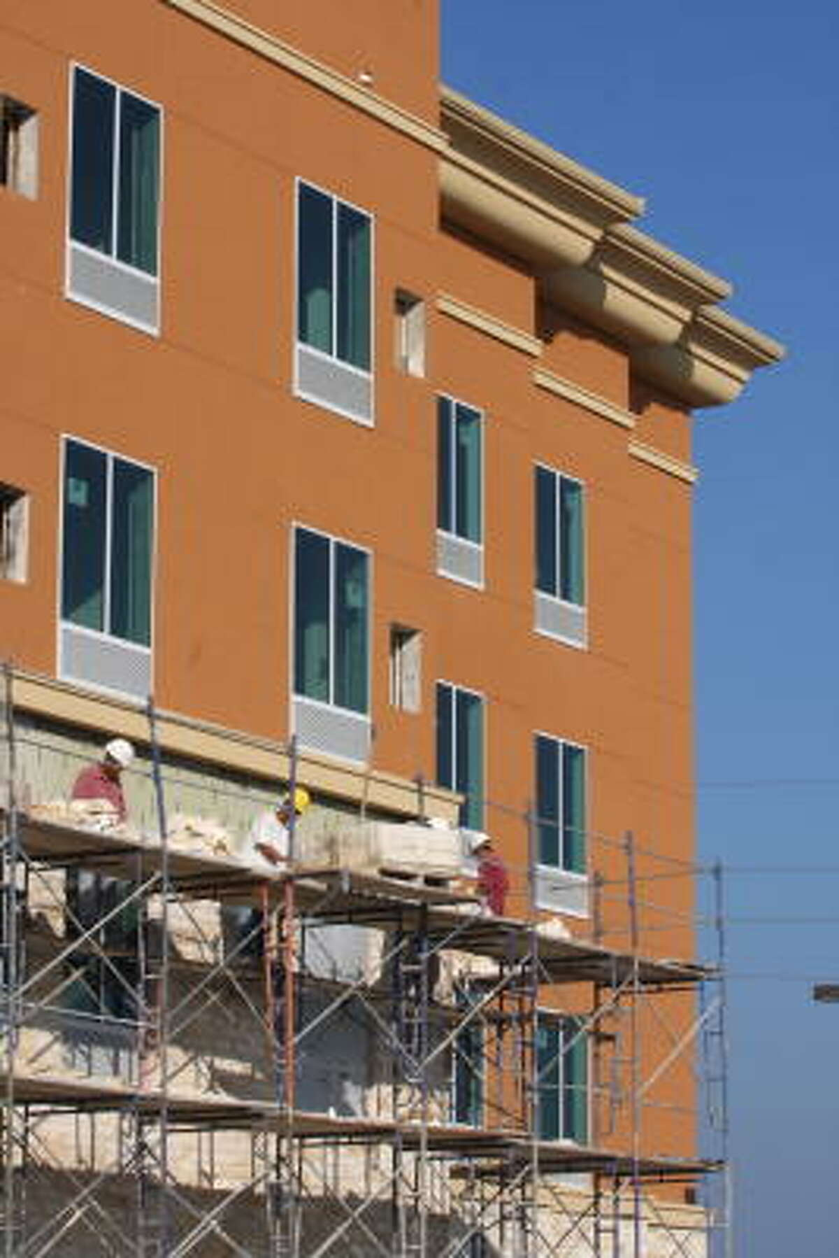Bricklayers are installing brick to the outside of the Hilton Garden Inn on Market Place Drive near Katy Mills mall. The hotel is scheduled to be completed in December.