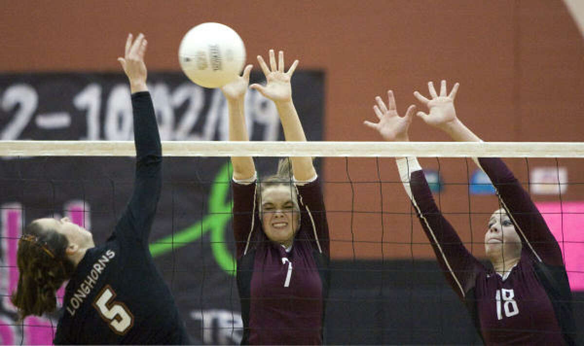 Pearland's Kat Evans (7) and Autumn Taylor (18) leap to block a shot by Dobie's Katherine Finney (5).